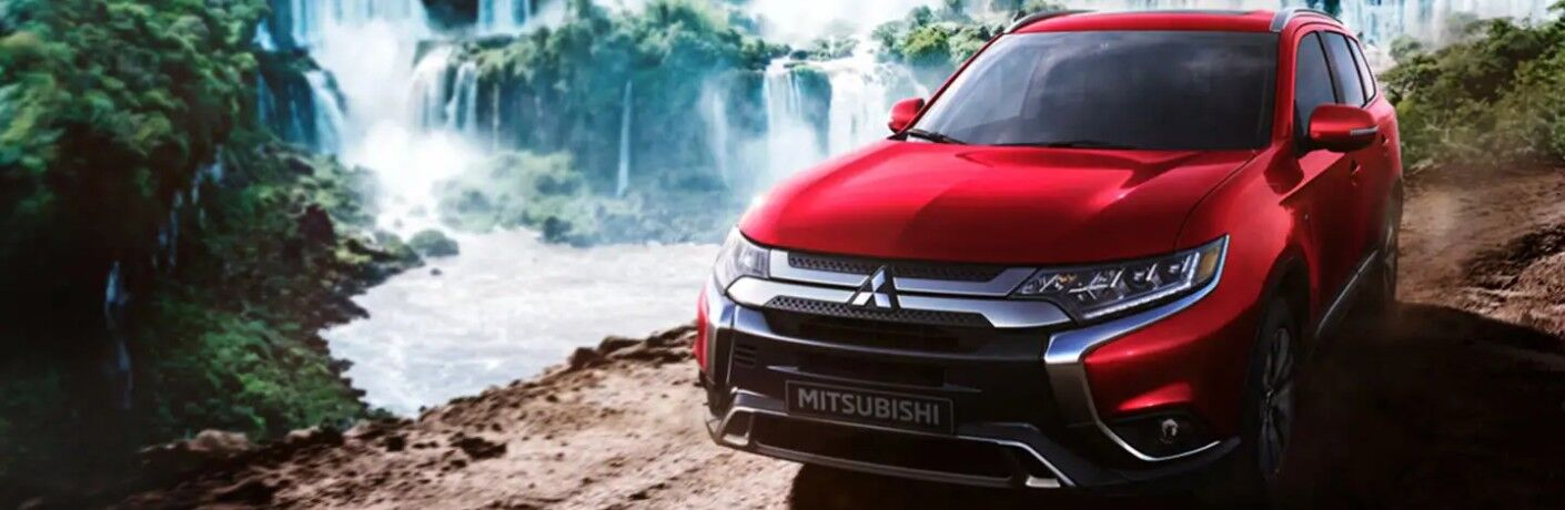 Front driver angle of a red 2020 Mitsubishi Outlander driving by a cliff with waterfalls in the background