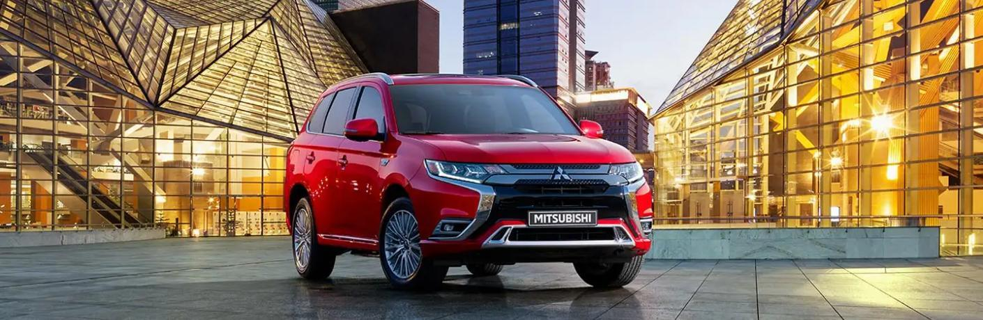 Front passenger angle of a red 2020 Mitsubishi Outlander PHEV with a city in the background