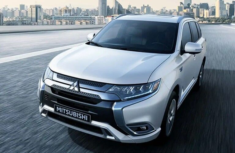Front driver angle of a white 2020 Mitsubishi Outlander PHEV driving down a road