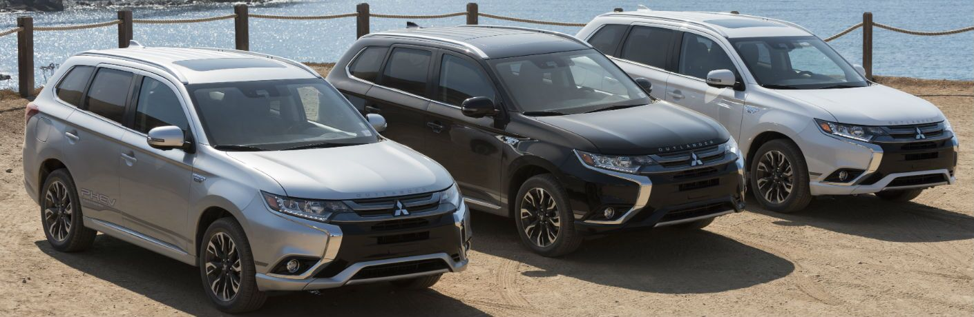 three 2018 Mitsubishi Outlander PHEV models parked next to water