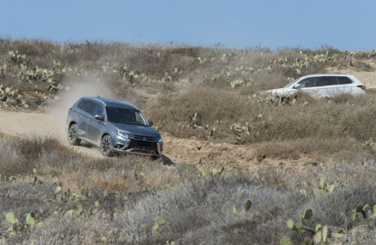 two 2018 Mitsubishi Outlander PHEVs driving off-road in a dirt field