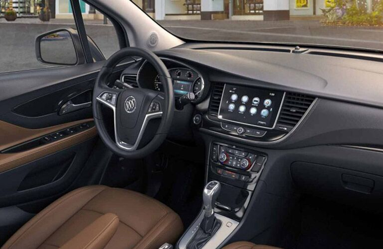 Interior view of a 2018 Buick Encore showing the brown seating, steering wheel and touchscreen