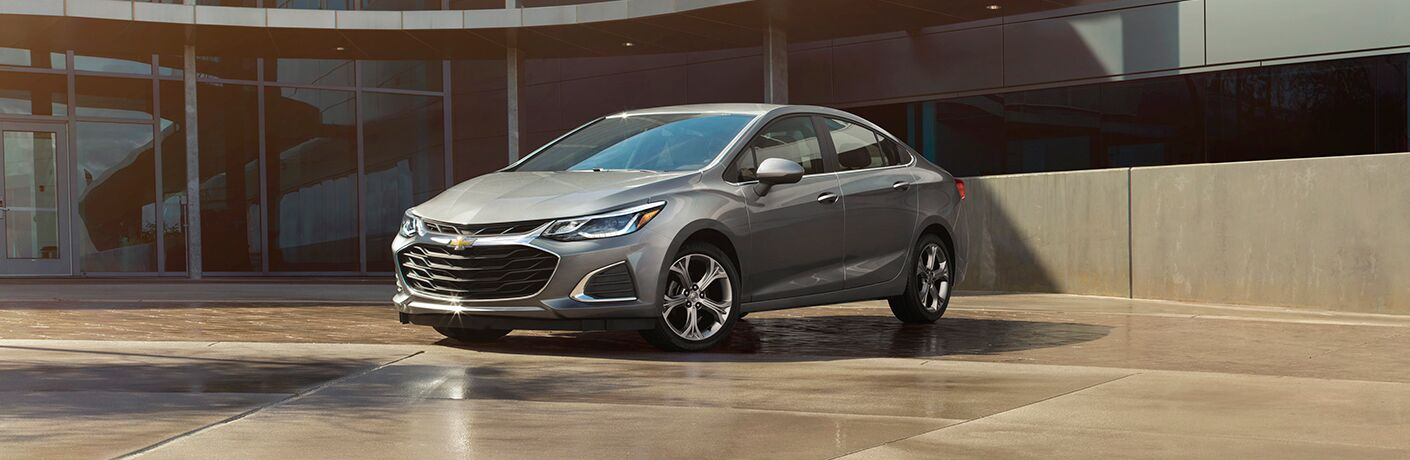 Exterior view of a gray 2019 Chevrolet Cruze parked outside an office building