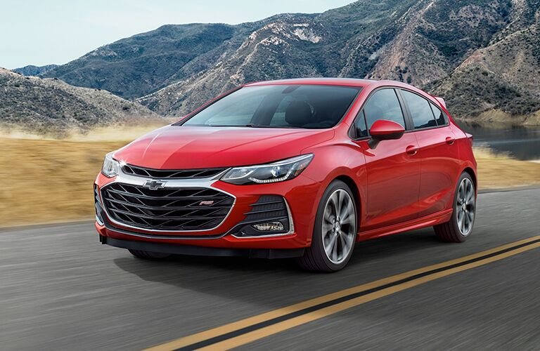 Exterior view of a red 2019 Chevrolet Cruze hatchback driving down a two-lane highway