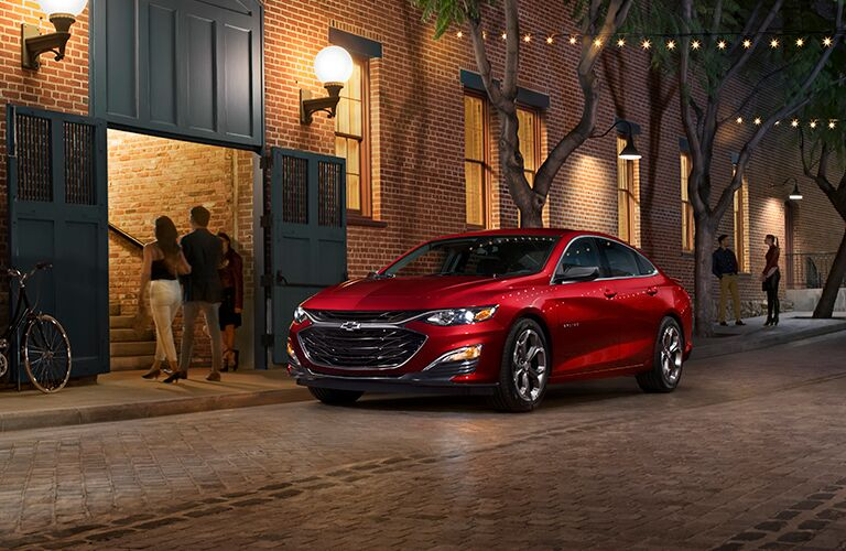 Red 2019 Chevrolet Malibu parked in front of a stone building at night