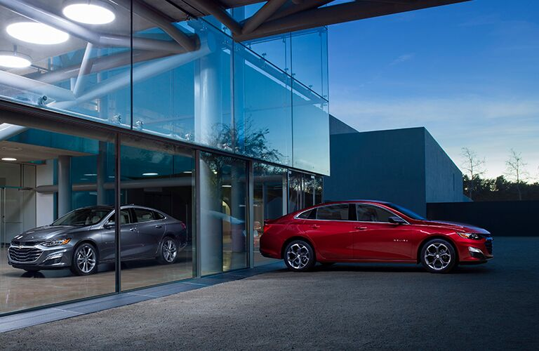 Red 2019 Chevrolet Malibu outside the galss, and grey 2019 Chevrolet Malibu inside glass