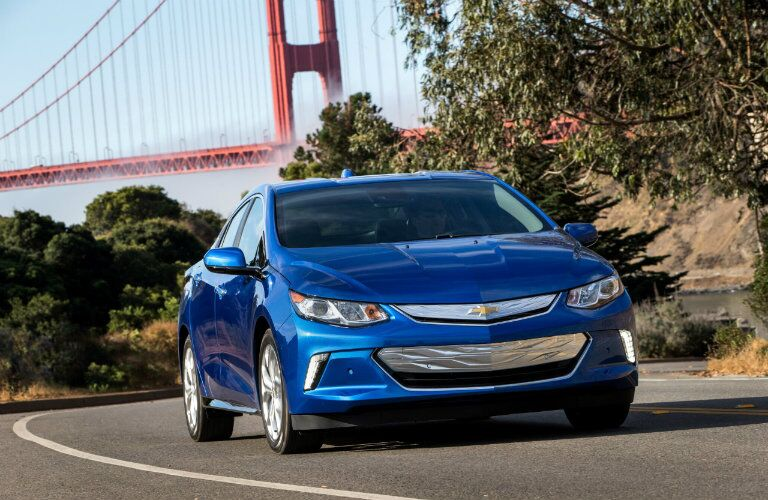Blue Chevy Volt driving with a bridge in the back