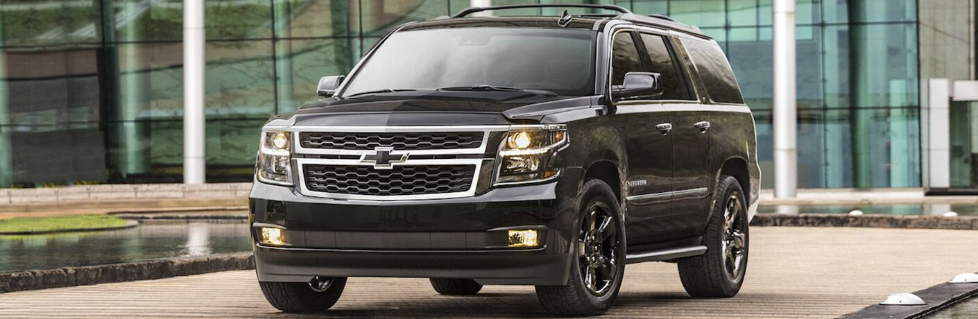 Black 2018 Chevrolet Suburban parked in front of a glass building