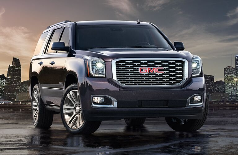 Exterior view of a black 2018 GMC Yukon parked on wet pavement with skyscrapers in the background