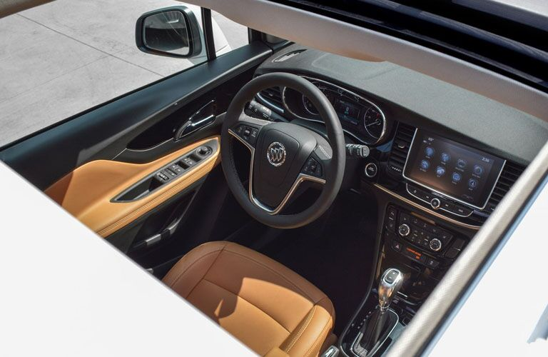 Interior view of the steering wheel through the open moonroof of a 2019 Buick Encore