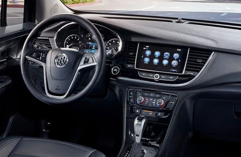 Interior view of the black steering wheel and touchscreen inside a 2019 Buick Encore