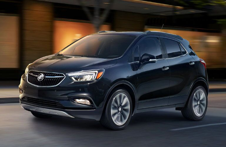 Exterior view of a blue 2019 Buick encore driving down a city street at night