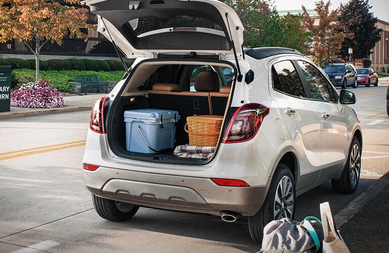 Exterior view of the rear of a white 2019 Buick Encore with the liftgate open and cargo inside