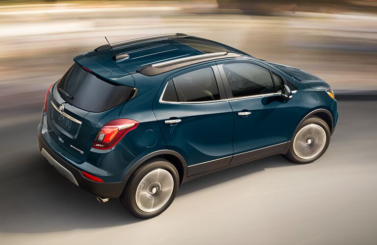 Exterior view of the rear of a teal 2019 Buick Encore driving down the highway