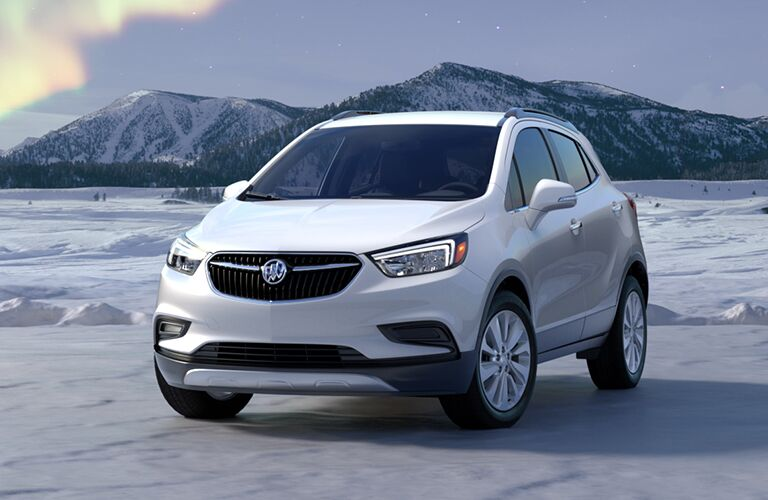 Exterior view of the front of a white 2019 Buick Encore parked on snowy terrain with mountains in the background