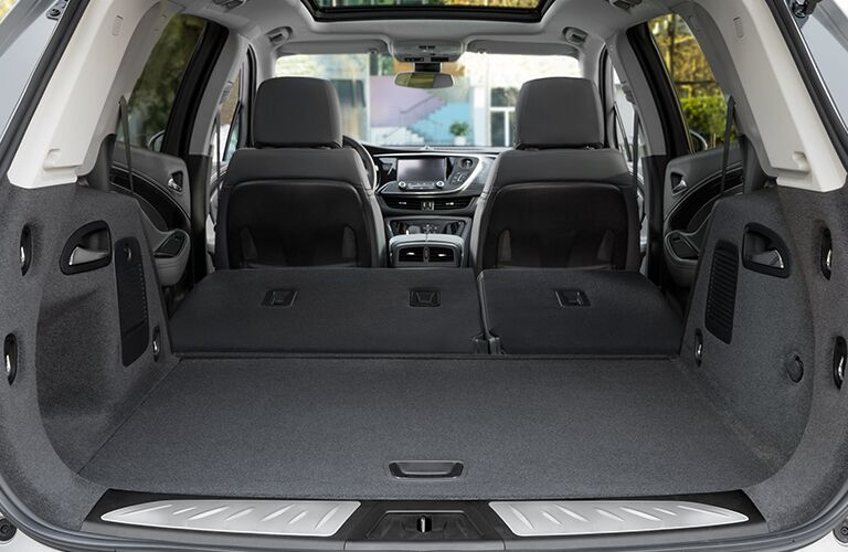 Interior view of the rear cargo space of a 2019 Buick Envision with the rear seating folded flat