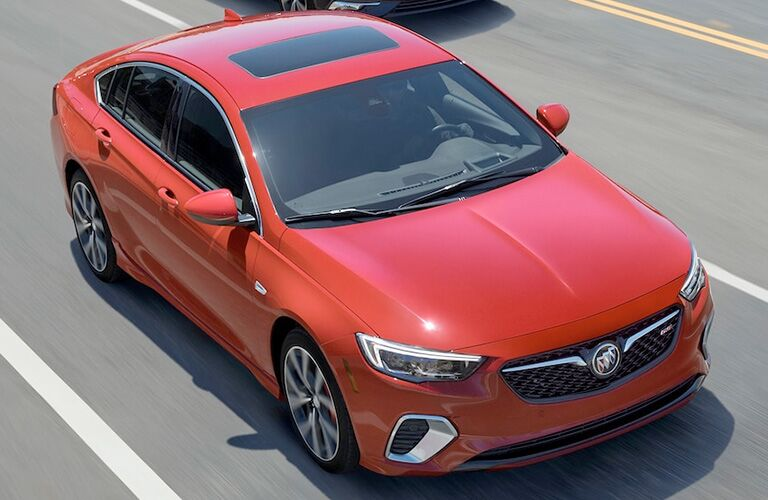 Exterior view of a red 2019 Buick Regal GS driving down a four-lane street