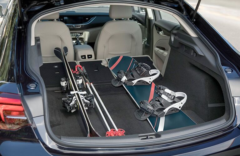 Interior view of a 2019 Buick Regal Sportback with the rear seats folded flat to haul snow skis and a snowboard