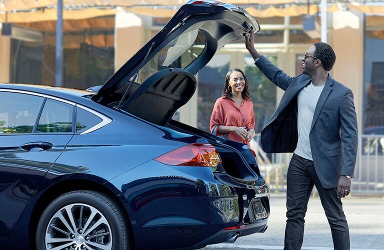 Exterior view of a black 2019 Buick Regal Sportback with the hatch open and a couple loading cargo