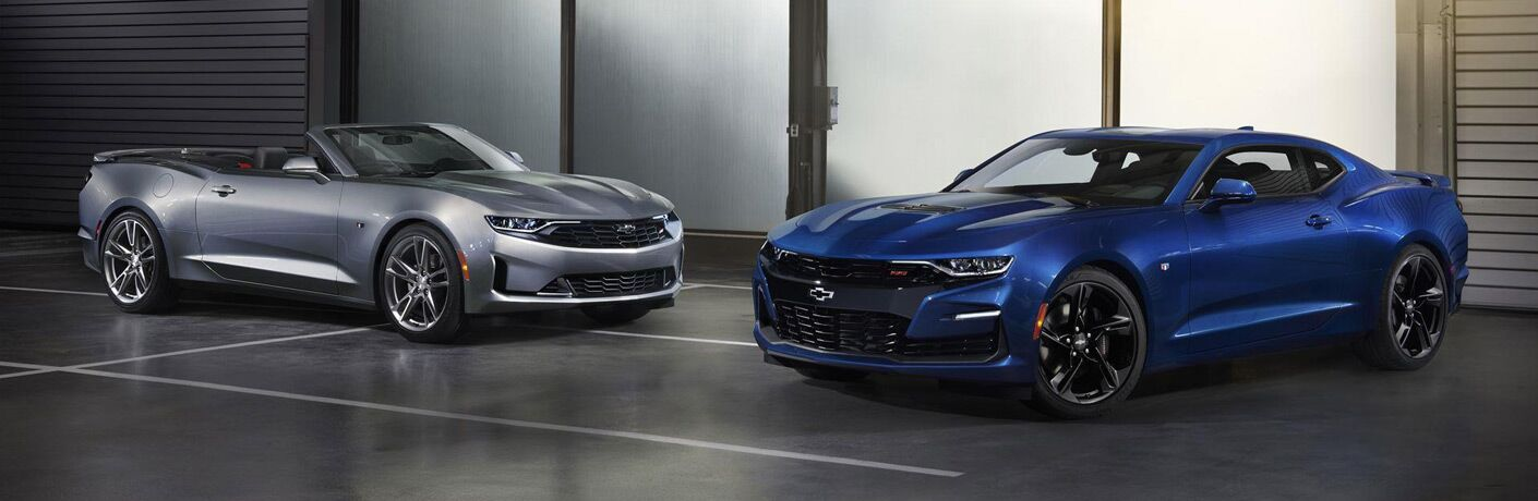 Exterior view of a silver 2019 Chevrolet Camaro Convertible and a blue 2019 Chevrolet Camaro parked in a showroom