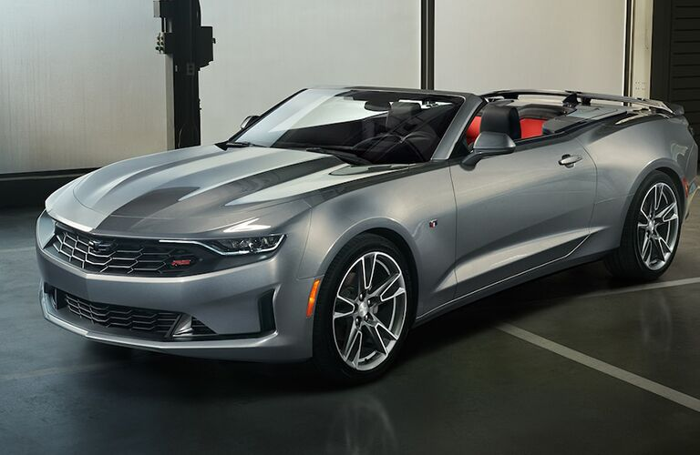 Exterior view of a silver 2019 Chevrolet Camaro Convertible parked in a parking garage