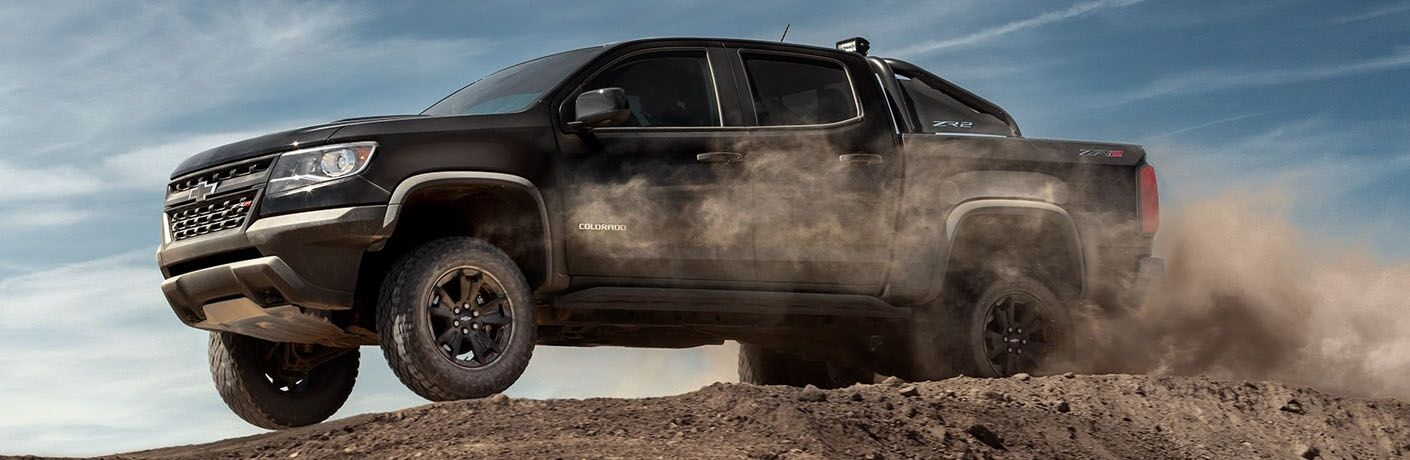 Exterior view of a black 2019 Chevrolet Colorado driving on dirt terrain