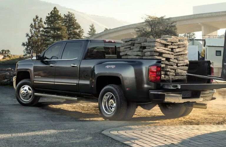 Exterior view of a black 2019 Chevrolet Silverado 3500HD hauling several bricks in the truck bed