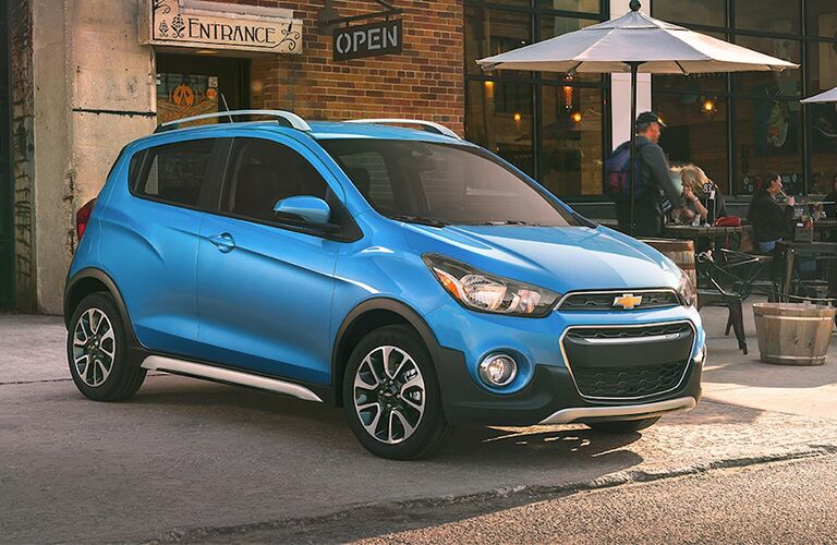 Blue 2019 Chevrolet Spark parked next to an outdoor restaurant