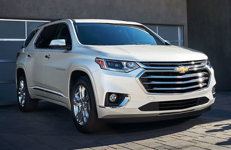 Exterior view of the front of a white 2019 Chevrolet Traverse parked outside the garage in a driveway