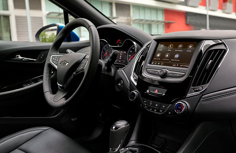 Interior view of the black steering wheel and touchscreen inside of a 2019 Chevrolet Cruze