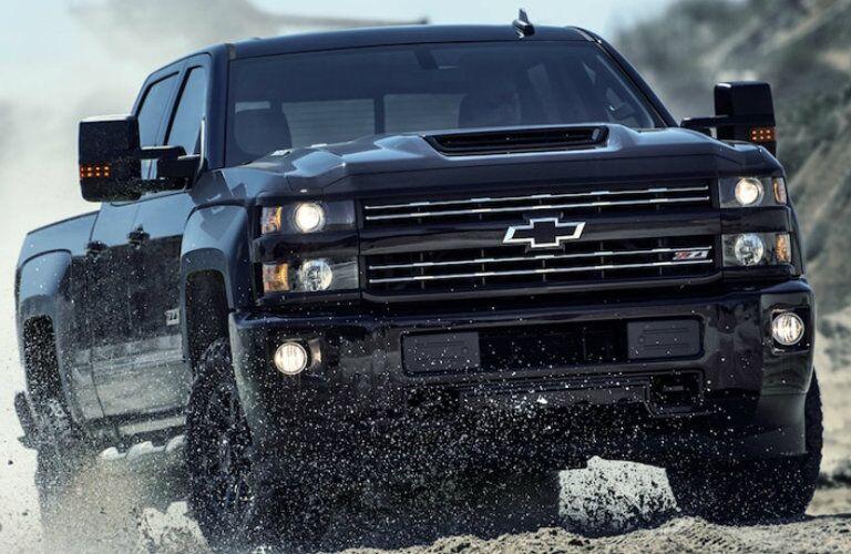 Exterior view of a black 2019 Chevrolet Silverado 2500HD driving through mud