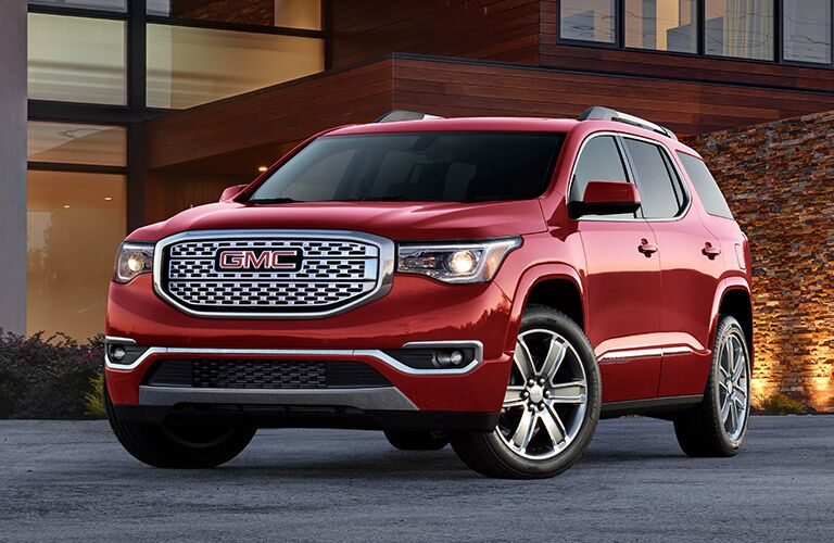 Exterior view of the front of a red 2019 GMC Acadia parked in a driveway with house in the background