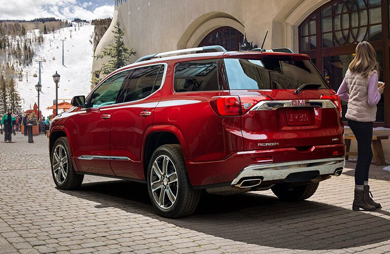 Exterior view of the rear of a red 2019 GMC Acadia parked on a brick street with a woman walking nearby