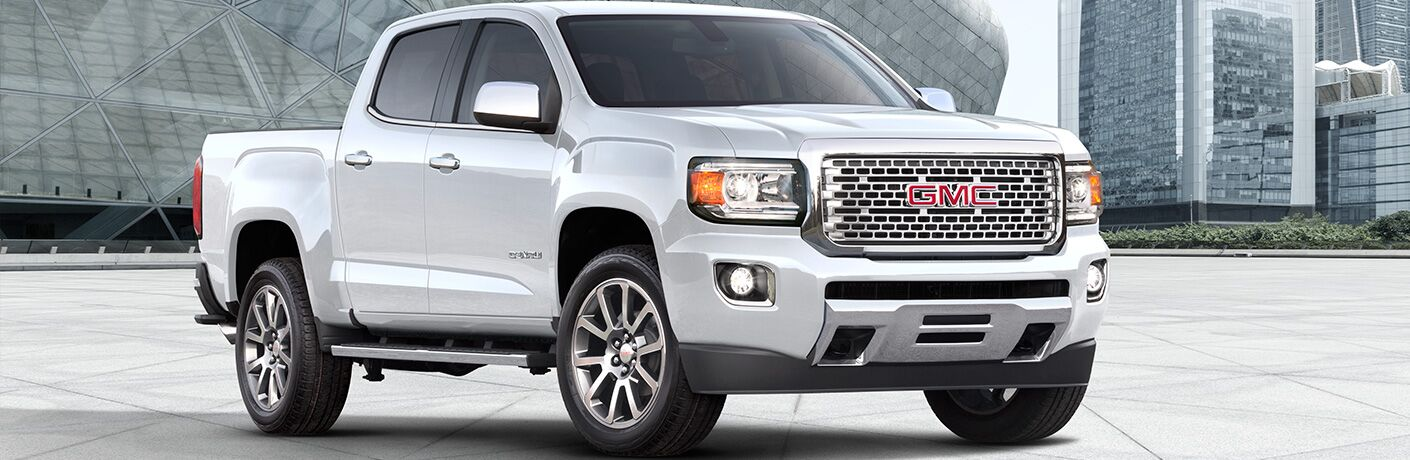 Exterior view of a white 2019 GMC Canyon parked outside several large buildings in the city