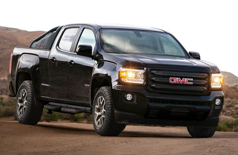 Exterior view of the front of a black 2019 GMC Canyon parked near large hills and mountains