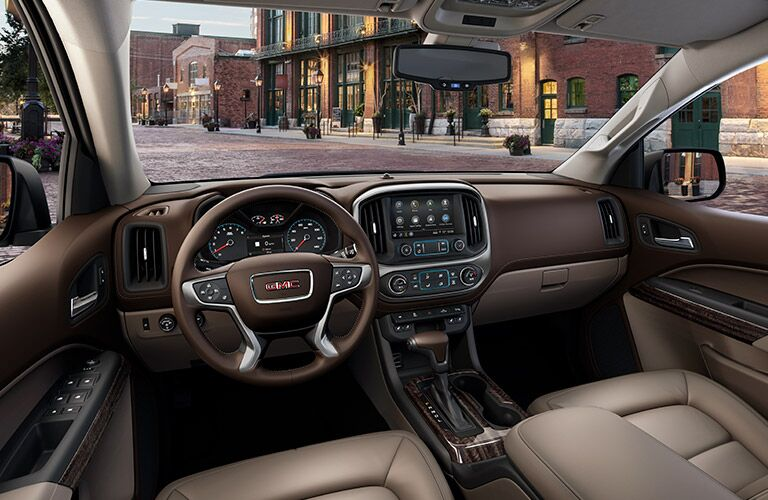 Interior view of the tan seating, steering wheel, and touchscreen inside a 2019 GMC Canyon