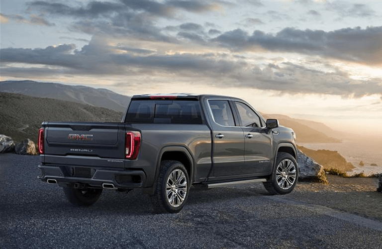 Exterior view of the rear of a dark gray 2019 GMC Sierra 1500 parked on gravel with clouds in the background