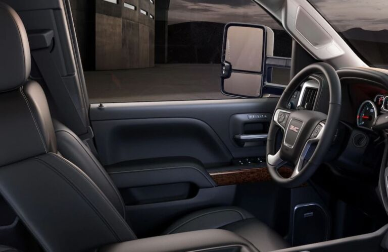 Interior view of the steering wheel and front seating inside a 2019 GMC Sierra 2500HD