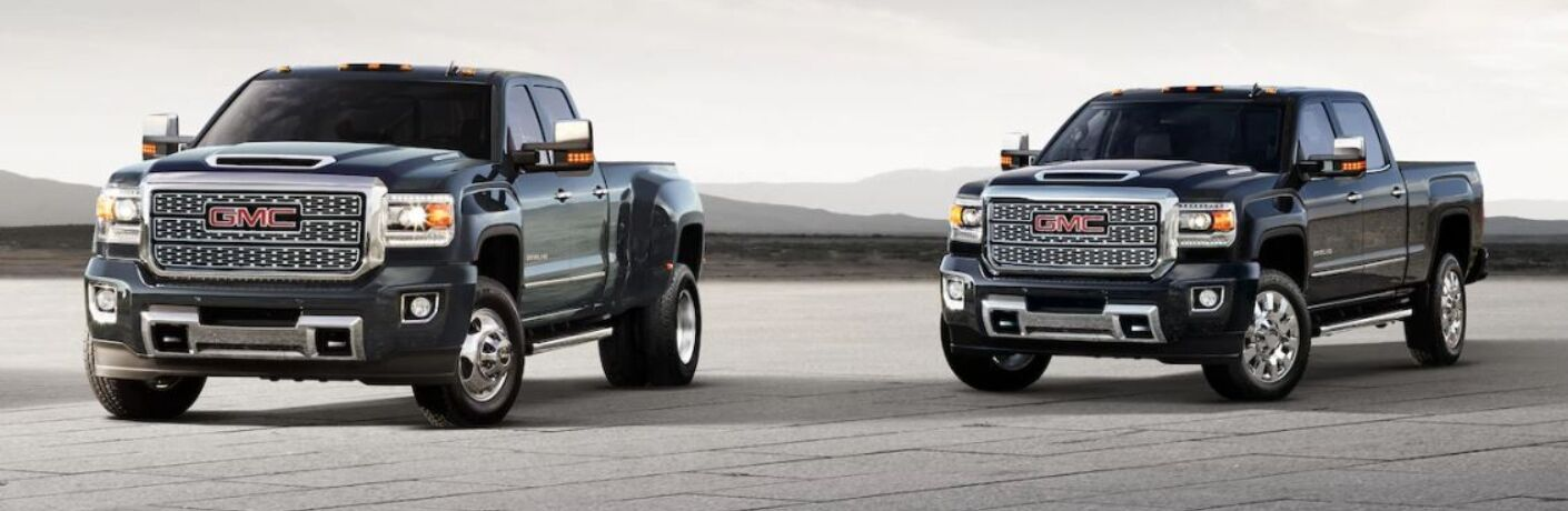 Exterior view of two black 2019 GMC Sierra HD models parked in an empty concrete lot