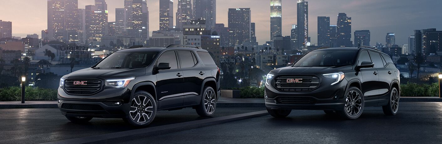 Exterior view of two black 2019 GMC Terrain models parked outside the city with skyscrapers in the background