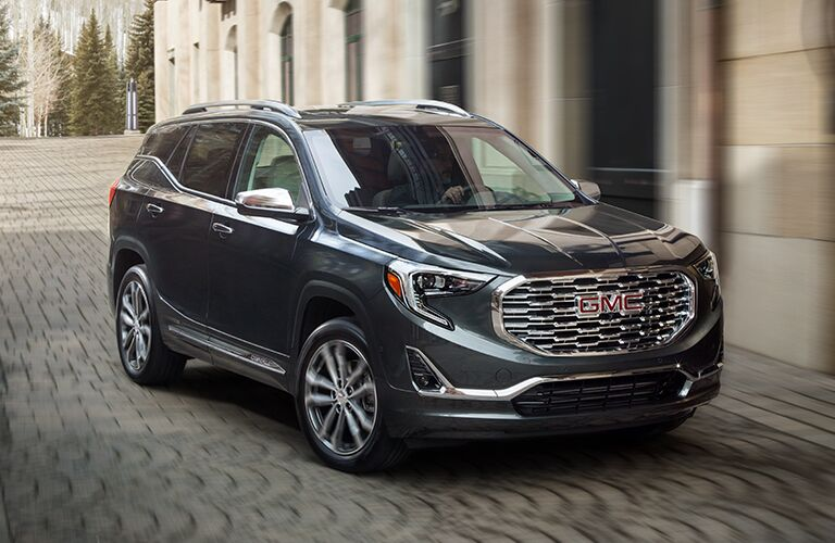 Exterior view of a gray 2019 GMC Terrain driving on a brick alley in the city