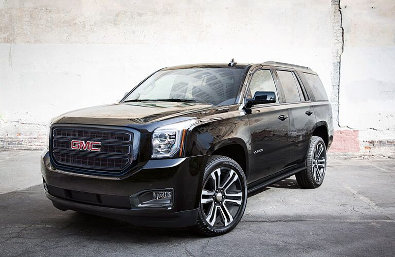 Exterior view of a black 2019 GMC Yukon parked near a concrete wall in an alley