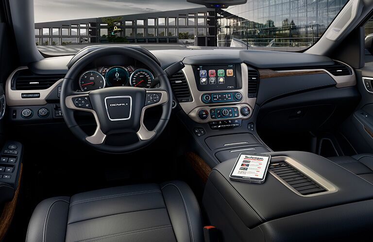 Interior view of the black steering wheel and touchscreen inside a 2019 GMC Yukon
