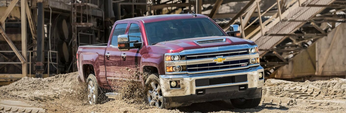 Exterior view of a red 2019 Chevrolet Silverado HD driving through a muddy surface at a job site