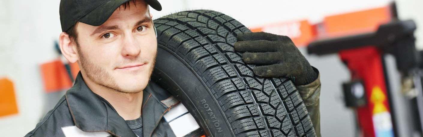 Handsome mechanic holding tire