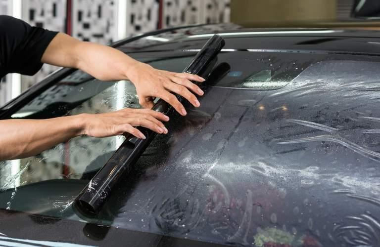 Body shop staff laying window tint
