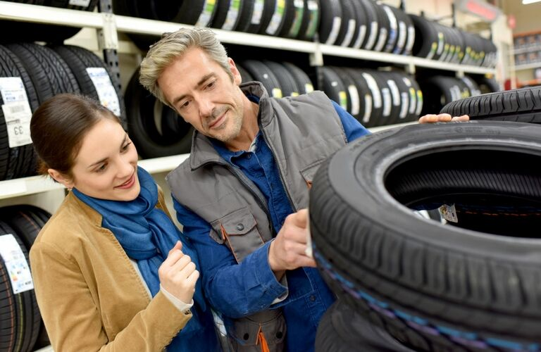 Service person and customer look at a tire