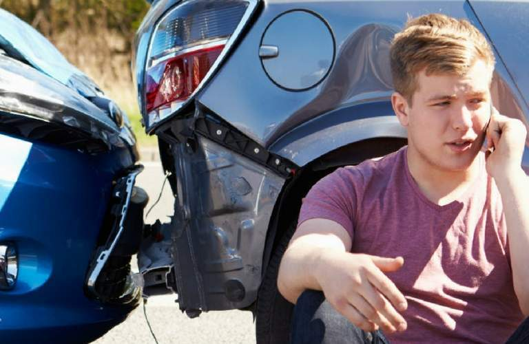 Young driver on phone in front of a crash