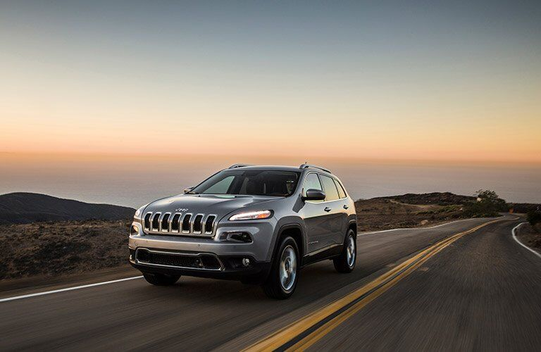gray 2017 Jeep Cherokee driving on road