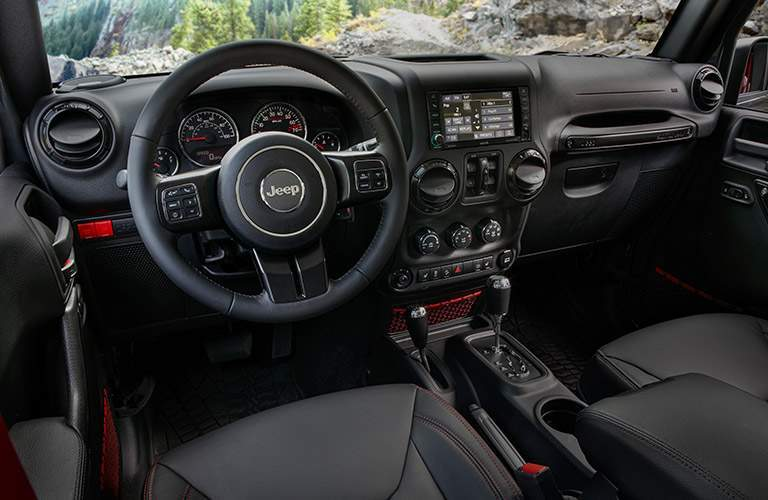 interior of 2018 jeep wrangler jk rubicon shown featuring infotainment system and steering wheel in black leather color